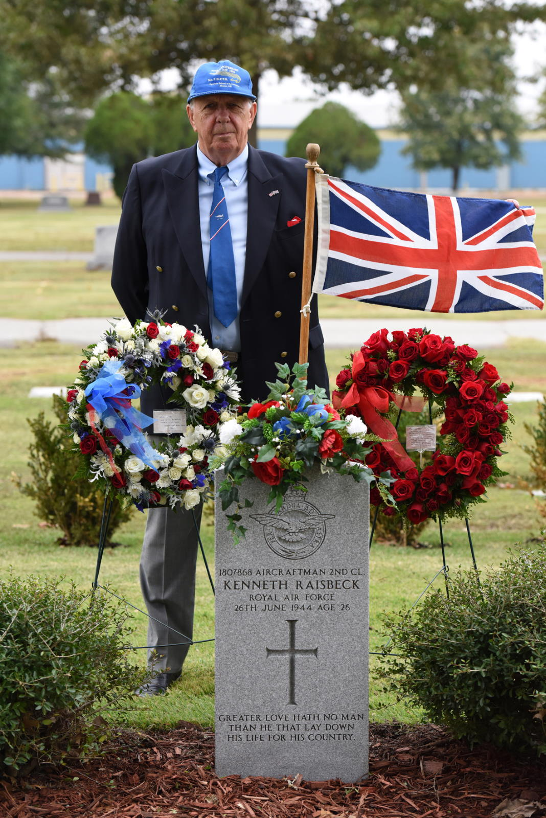 John Raisbeck son of British Cadet Kenneth Raisbeck standing next to his fathers grave marker with floral wreaths and flag of England
